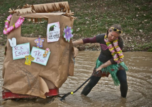 Photo of Michelle dragging a home-made tiki bar through the mud